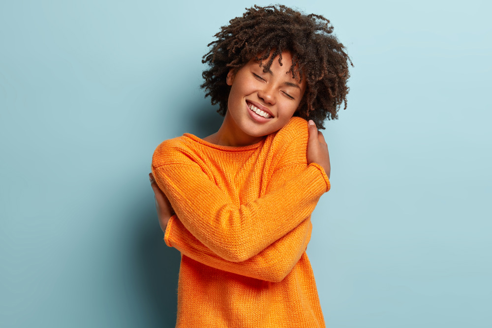 charming-gorgeous-afro-woman-keeps-eyes-closed-smiles-with-pleasure-shows-white-teeth-feels-comfort-hugs-herself-wears-orange-jumper-tilts-head-models-over-blue-wall-has-high-self-esteem